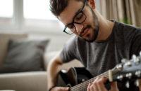 man singing softly and playing guitar