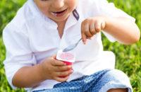 child sitting in grass eating yogurt