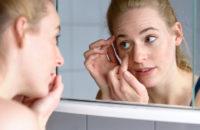 Woman examining puffy eye in mirror