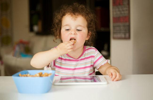 Child on ipad eating snack