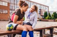 Trainer checks on injured athlete at school