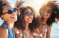 3 dark-skinned women laughing at the beach