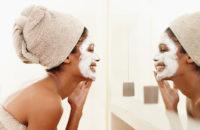 woman applying face mask in bathroom mirror
