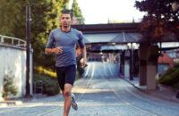 man running alone down a city street