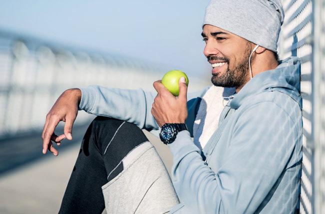 man on exercise break eating apple
