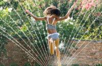 child runs through sprinkler during summer